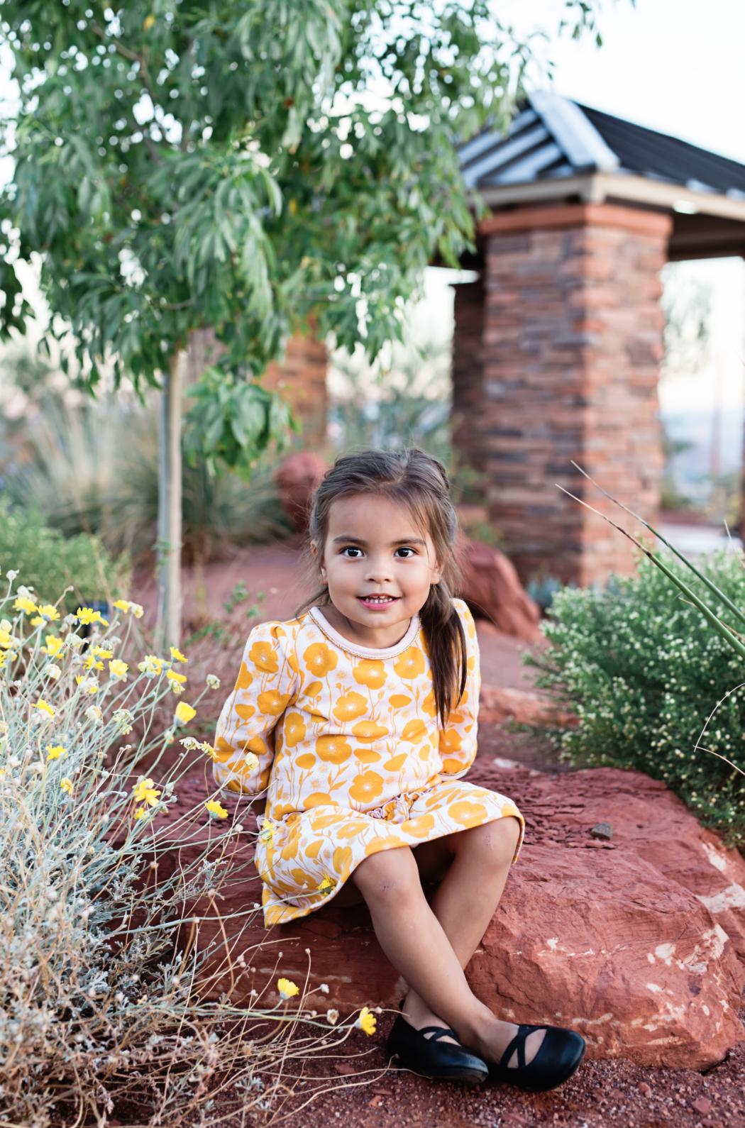 little-girl-sitting-on-a-rock