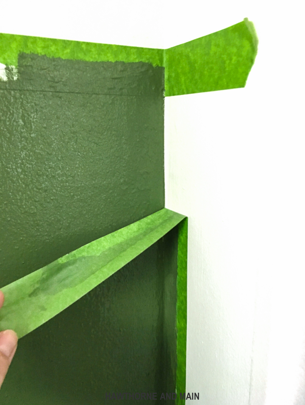 pulling-off-frog-tape-on-a-green-wall