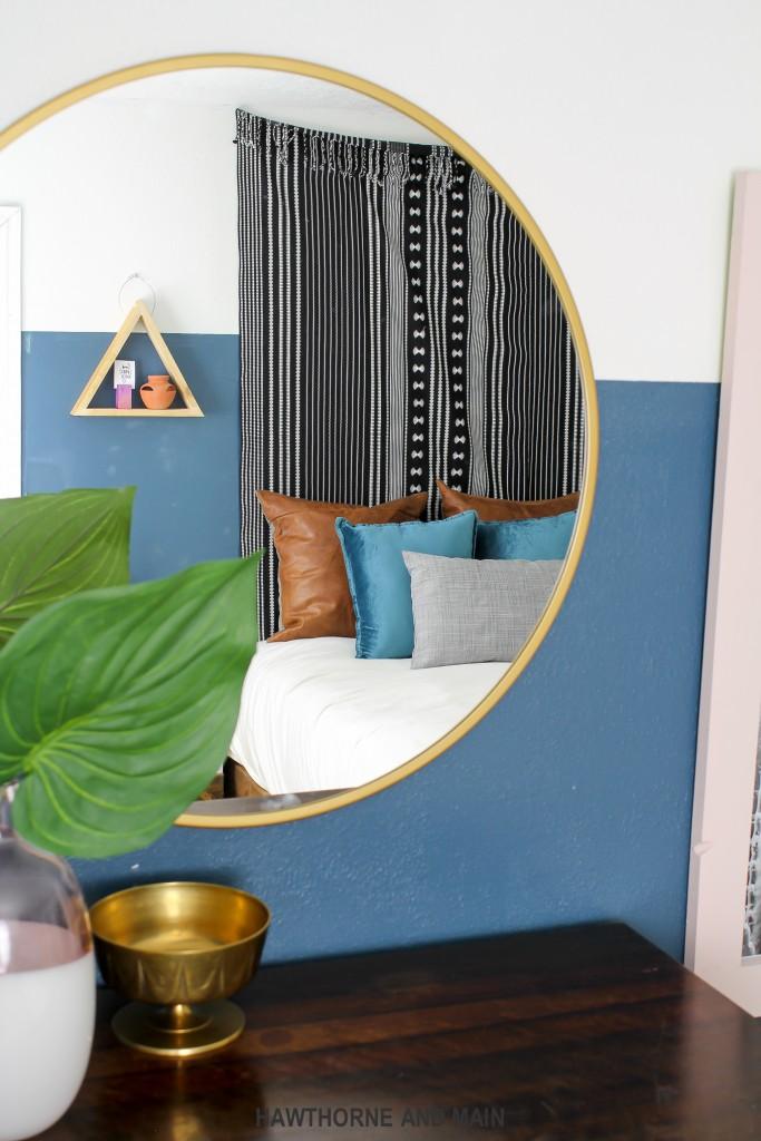 round-brass-mirror-in-a-bedroom